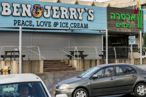 """Motorists drive past a closed """"Ben & Jerry's"""" ice-cream shop in the Israeli city of Yavne, about 30 kilometres south of Tel Aviv, on July 23, 2021. [AHMAD GHARABLI/AFP via Getty Images]"""
