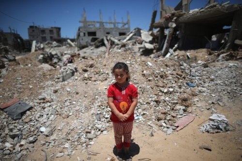 Fatima Shamaly, aged four, stands amongst the devastation and rubble during a music workshop for traumatised children [Christopher Furlong/Getty Images]