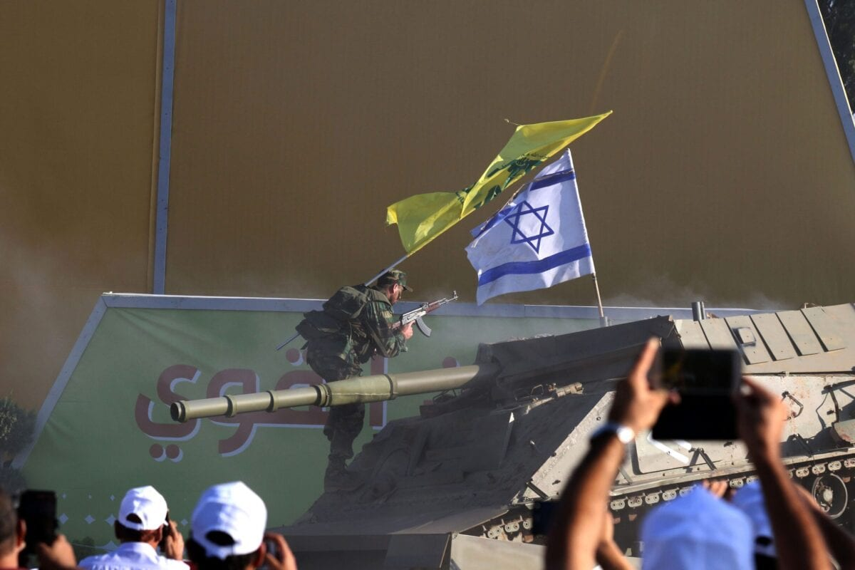 Supporters watch as members of the Lebanese Shia movement Hezbollah perform a reenactment of an attack on an Israeli tank to mark the 11th anniversary of the end of the 2006 war with Israel, in the village of Khiam in southern Lebanon on August 13, 2017 [MAHMOUD ZAYYAT/AFP via Getty Images]