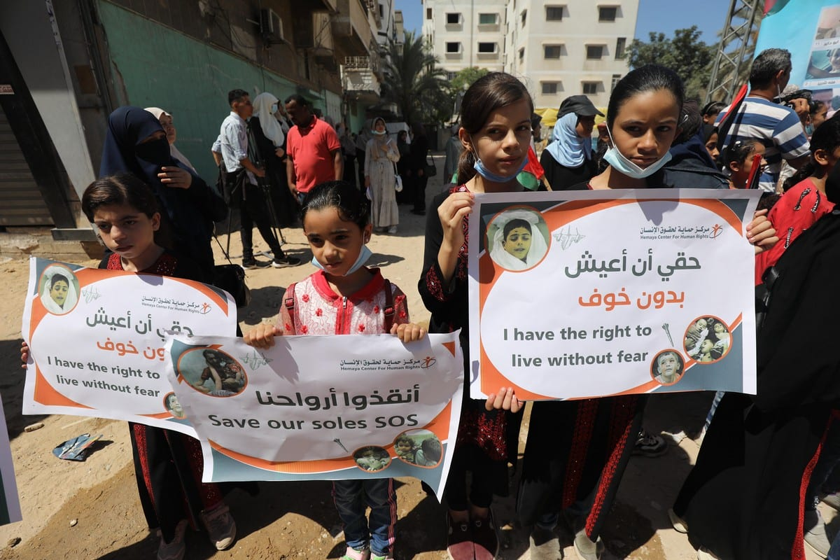 Palestinians launch the 'Save the Children of Gaza' initiative by raising pictures of minors killed in Israel's latest aggression against the Strip in May 2021 [Mohammed Asad/Middle East Monitor]