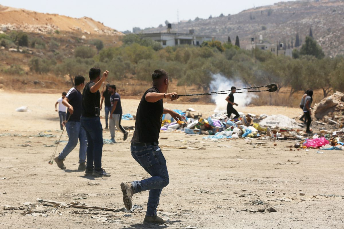 Palestinians throw stones in response to Israeli forces' intervention towards Palestinian protestersin Nablus, West Bank on August 02, 2021 [Nedal Eshtaya/Anadolu Agency]