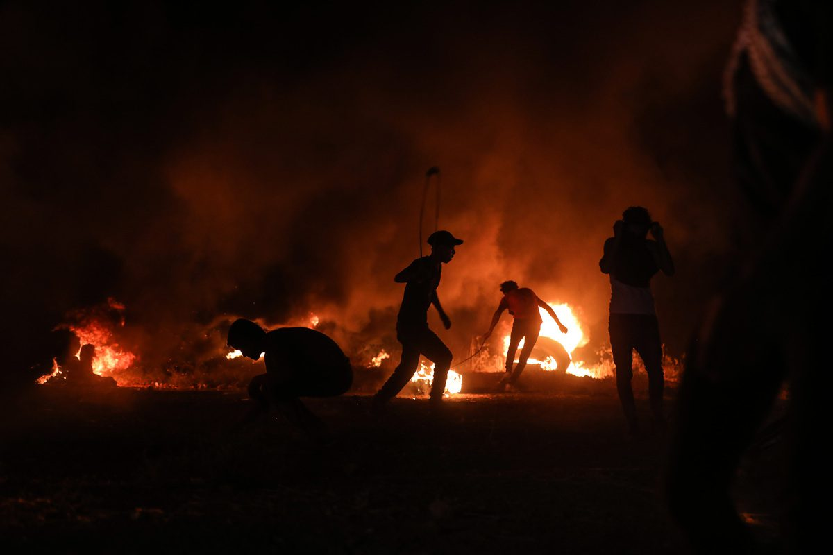Palestinian demonstrators burn tyres and throw stones during a protest against Israel's blockade of Gaza, as Israeli soldier shoot at them, along the eastern border of the Gaza Strip, in Gaza City, Gaza on August 28, 2021 [Mustafa Hassona / Anadolu Agency]