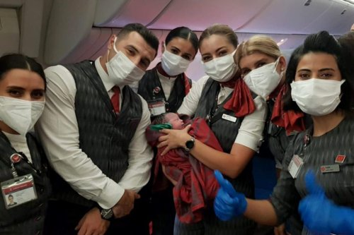 Cabin crew poses for a photo with the Afghan baby born on board of Turkish Airlines Dubai-Birmingham evacuation flight at 10,000 feet on August 28, 2021 [Turkish Airlines/Anadolu Agency]