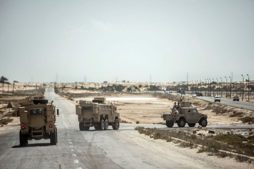 A picture taken on July 26, 2018 shows Egyptian policemen driving on a road leading to the North Sinai provincial capital of El-Arish. [KHALED DESOUKI/AFP via Getty Images]