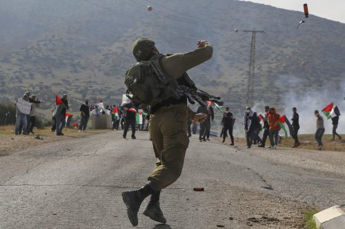 An Israeli soldier throws teargas against Palestinian protesters during a protest against Jewish settlements on November 24, 2020, in the Jordan Valley in the Israeli-occupied West Bank [JAAFAR ASHTIYEH/AFP via Getty Images]