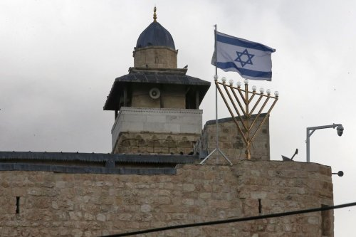 A Hanukkah menorah is picture next to an Israeli flag on the top roof of the Ibrahimi mosque, also known to Jews as the Cave of the Patriarchs, in the divided West Bank town of Hebron on 9 December 2020. [HAZEM BADER/AFP via Getty Images]