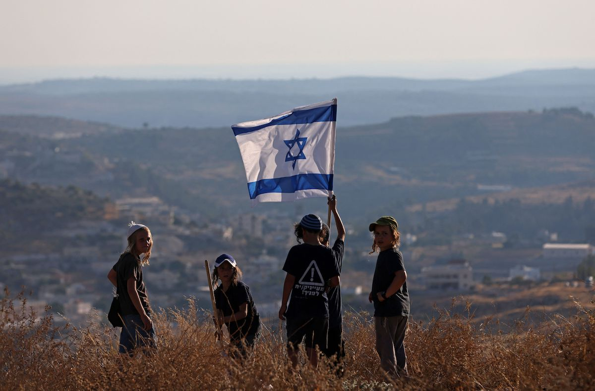 """Children of Israeli settlers wave a national flag near the settlement of Bat Ayin in the occupied West Bank on 21 June 2021, as right-wing activists and settler leaders hold 14 simultaneous marches to stop """"Arab control"""" in Area C. [EMMANUEL DUNAND/AFP via Getty Images]"""