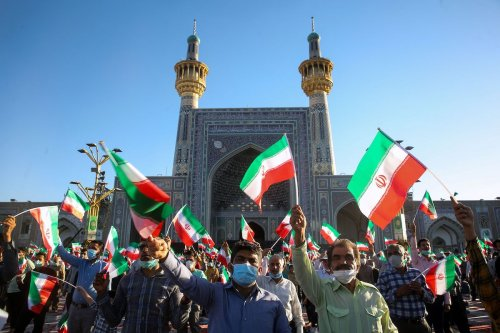 Supporters of Iran's President-elect Ebrahim Raisi cheer at the Imam Reza shrine in the city of Mashhad in northeastern Iran, on 22 June 2021. [MOHSEN ESMAEILZADEH/ISNA NEWS AGENCY/AFP via Getty Images]