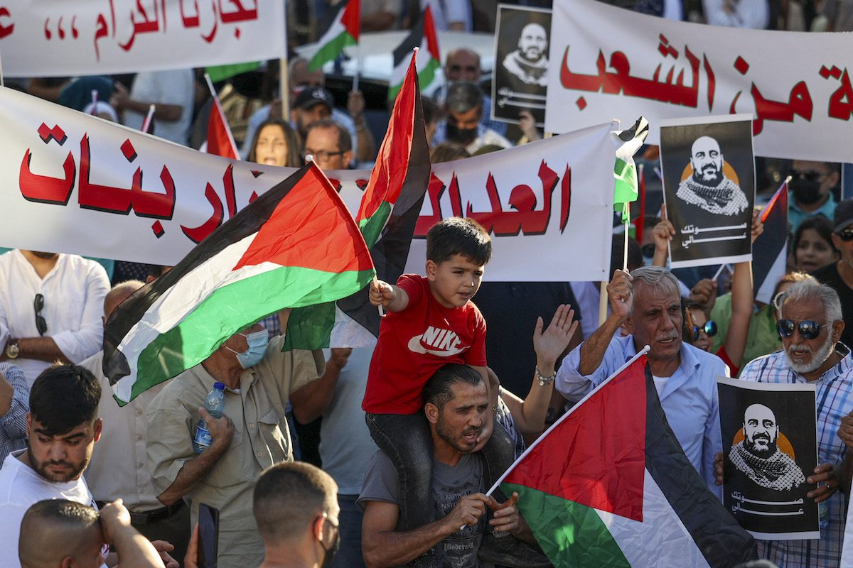Palestinian protesters rally in Ramallah city in the occupied West Bank on July 17, 2021, denouncing the Palestinian Authority (PA) in the aftermath of the death of activist Nizar Banat while in the custody of PA security forces. [ABBAS MOMANI/AFP via Getty Images]
