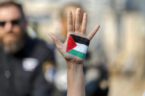A demonstrator raises her hand, painted with the colours of the Palestinian flag, during a demonstration by Palestinian, Israeli, and foreign activists against Israeli occupation and settlement activity in the Palestinian Territories and east Jerusalem, in Jerusalem's Palestinian Sheikh Jarrah neighbourhood on 30 July 2021. [AHMAD GHARABLI/AFP via Getty Images]