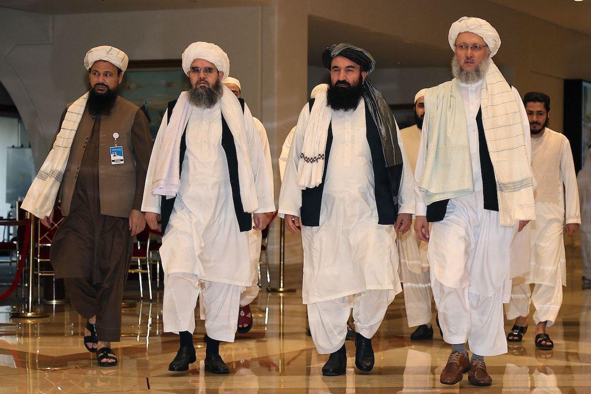 Head of the Taliban delegation Abdul Salam Hanafi (R), accompanied by Taliban officials (2R to L) Amir Khan Muttaqi, Shahabuddin Delawar and Abdul Latif Mansour, walks down a hotel lobby during the talks in Qatar's capital Doha on 12 August 2021. [KARIM JAAFAR/AFP via Getty Images]