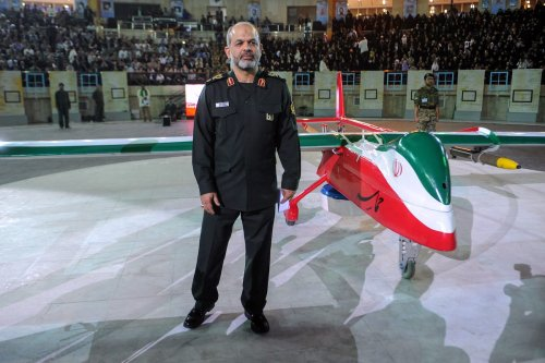 """Iranian Defence Minister Ahmad Vahidi stands next to the new Iranian made drone """"Epic"""" during a ceremony in Tehran on 9 May 2013. [HEMMAT KHAHI/AFP via Getty Images]"""