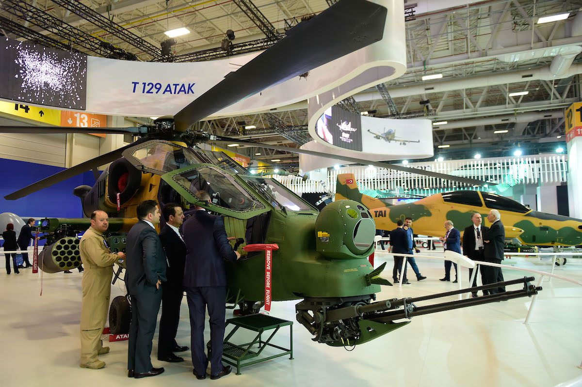 """People look at a Turkish attack helicopter """"T129 ATAK"""" on 9 May 2017 during the opening day of the 13th International Defense Industry Fair (IDEF) in Istanbul. [YASIN AKGUL/AFP via Getty Images]"""