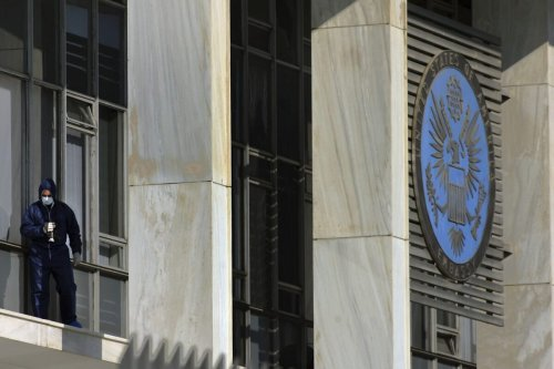 ATHENS, GREECE - JANUARY 12: An anti-terrorist investigator searches for evidence inside the US Embassy in Athens after unknown assailants fired a rocket into the facility, causing damage to the building but no casualties, on January 12, 2007 in Athens, Greece. Police sources said the self-propelled explosive penetrated the building near the emblem at the front-entrance and exploded inside, damaging a toilet on the third floor. Police are investigating claims that a left-wing radical group is responsible. (Photo by Milos Bicanski/Getty Images)