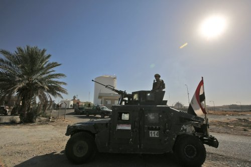 A member of the Iraqi government forces stands guard in a humvee turret while guarding the Bai Hassan oil field, west of the multi-ethnic northern Iraqi city of Kirkuk, on October 19, 2017 [AHMAD AL-RUBAYE/AFP via Getty Images]