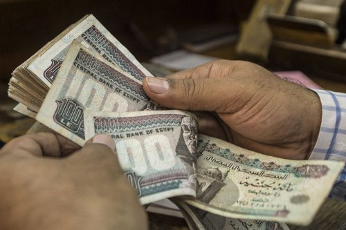 A man counts Egyptian pounds at currency exchange shop in downtown Cairo on 3 November 2016 [KHALED DESOUKI/AFP/Getty Images]