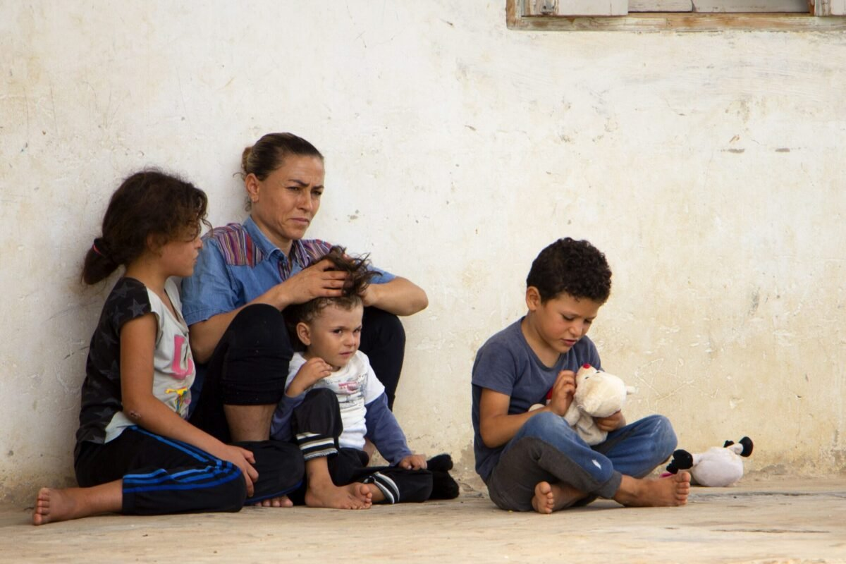 Tunisian mother and 3 of her children, sit in front of their house, in a popular neighbourhood of the eastern Tunisian port city of Sfax, on September 11, 2020 [HAMDI ZAGHDANE/AFP via Getty Images]