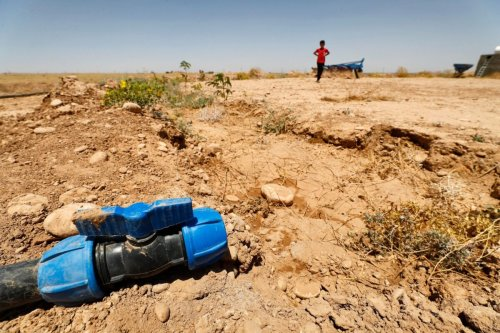A boy walks through a dried up agricultural field near a dry water hose in the Saadiya area, north of Diyala in eastern Iraq on June 24, 2021. - As Iraq bakes under a blistering summer heat wave, its hard-scrabble farmers and herders are battling severe water shortages that are killing their animals, fields and way of life. The oil-rich country, scarred by four decades of war, is also one of the world's most vulnerable to the climate crisis and struggles with a host of other environmental challenges. (Photo by AHMAD AL-RUBAYE / AFP) (Photo by AHMAD AL-RUBAYE/AFP via Getty Images)