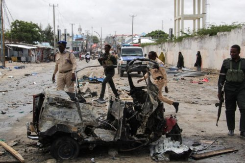 Police officers patrol by the wreckage of a car at the scene of suicide car bomb attack that targeted the city's police commissioner in Mogadishu, on July 10, 2021 [AFP via Getty Images]