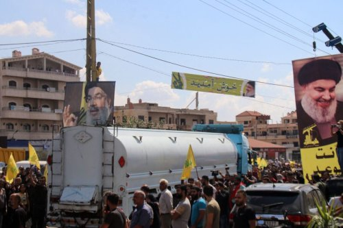 People raise portraits of the head of the Lebanese Shia movement Hezbollah Hassan Nasrallah, as they gather to welcome tankers carrying Iranian fuel, upon their arrival from Syria in the city of Baalbeck, in Lebanon's Bekaa valley, on September 16, 2021 [AFP via Getty Images]
