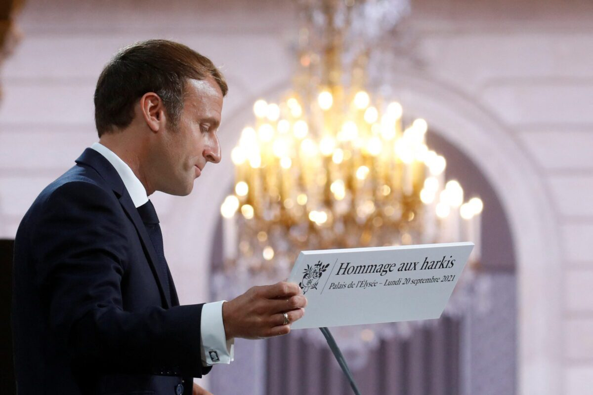 """French president Emmanuel Macron holds the sign reading """"Tribute to Harkis"""" as he delivers a speech during a ceremony in memory of the Harkis at the Elysee Palace in Paris, on September 20, 2021 [GONZALO FUENTES/POOL/AFP via Getty Images]"""