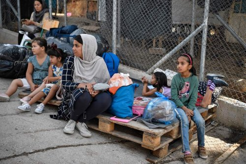 A family of refugees sit on their belongings at the old Samos camp, before being transferred to the new Samos RIC, the first of five new 'closed' migrant camps, on the island of Samos, Greece, on 20 September 2021. [LOUISA GOULIAMAKI/AFP via Getty Images]
