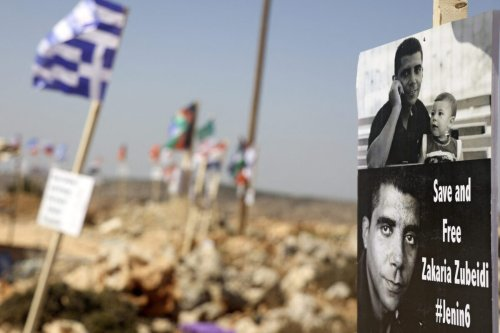 The picture of Palestinian prisoner Zakaria Zubeidi hangs of a flag in the occupied-West Bank town of Salfit on September 20, 201 [JAAFAR ASHTIYEH/AFP via Getty Images]