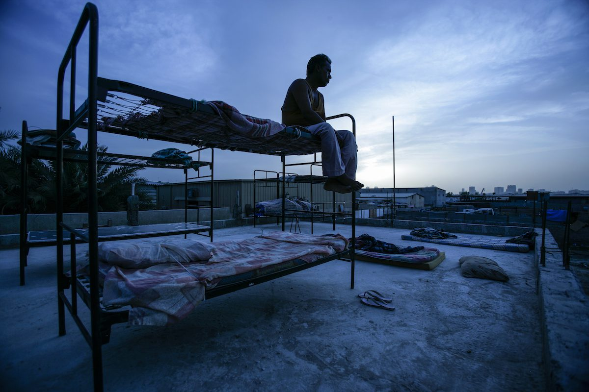 An abandoned migrant labourer sits on a rooftop in a squallid makeshift camp in Sharjah, the Emirate next to Dubai. [Brent Stirton/Getty Images]