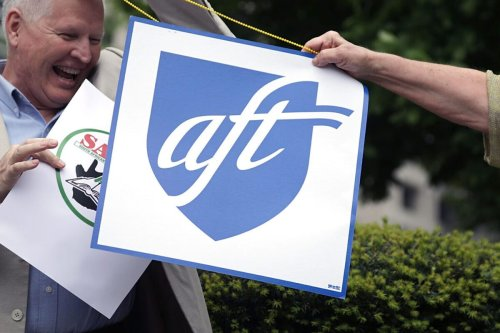 """WASHINGTON, DC - APRIL 21: Members of the American Federation of Teachers and teachers unions representatives from Uganda and South Africa rally outside the World Bank Group and International Monetary Fund Spring Meetings April 21, 2017 in Washington, DC. The demonstrators were protesting the World Bank's """"funding of Ôlow-feeÕ Bridge International Academies in poor African, Asian countries."""" (Photo by Chip Somodevilla/Getty Images)"""