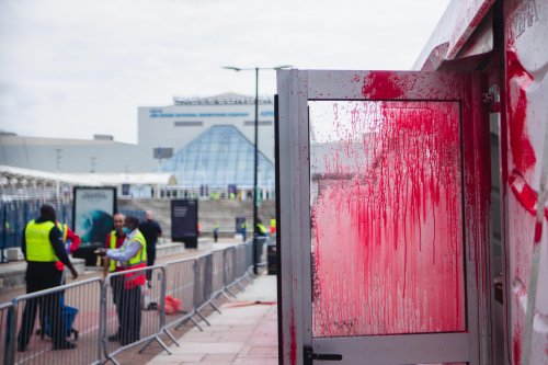 Palestine Action activists climbed on the fences of the Excel exhibition centre in London dyed-red blood security tent and threw red and green flares on Sunday, Sept 12, 2021 [VX Photo/ Vudi Xhymshiti]
