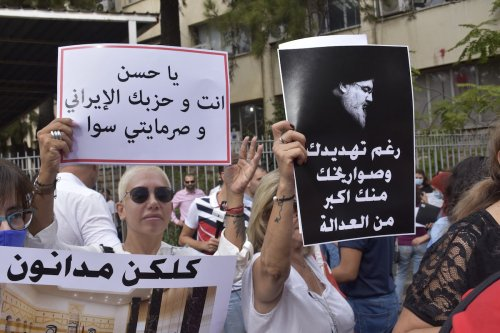 People holding banners stage a protest outside Beirut Palace of Justice to support the lead investigator Judge Tarek Bitar of last year's Beirut Port blast as they chant slogans against Hezbollah in Beirut, Lebanon on 13 October 2021. [Mahmut Geldi - Anadolu Agency]