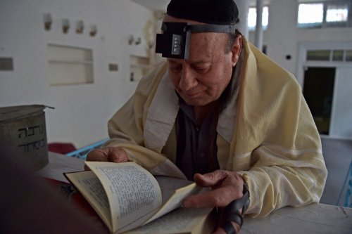Afghan Jew Zebulon Simentov looks at the Torah scripture at synagogue in Kabul, Afghanistan on 5 April 2021 [WAKIL KOHSAR/AFP/Getty Images]