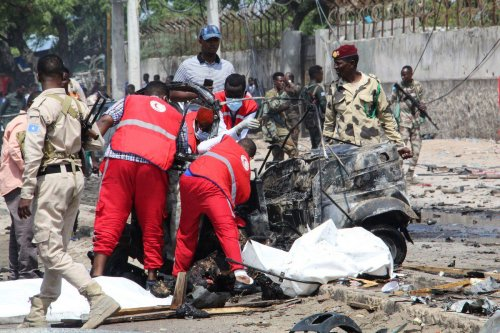 Medical workers and soldiers arrive at the scene of suicide car bomb attack in Mogadishu, Somalia on 10 July 2021 [AFP/Getty Images]