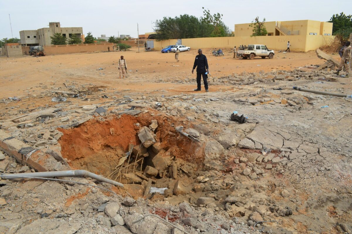 Malian soldiers stand near a hole in the ground caused by the explosion of a suicide car bomb attack overnight, which killed three people, on November 13, 2018, in Gao [STR/AFP via Getty Images]