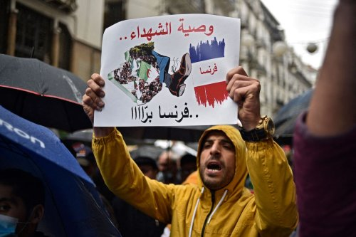 An Algerian holds an anti-France placard during an anti-government demonstration in the capital Algiers on 16 April 2021. [RYAD KRAMDI/AFP via Getty Images]