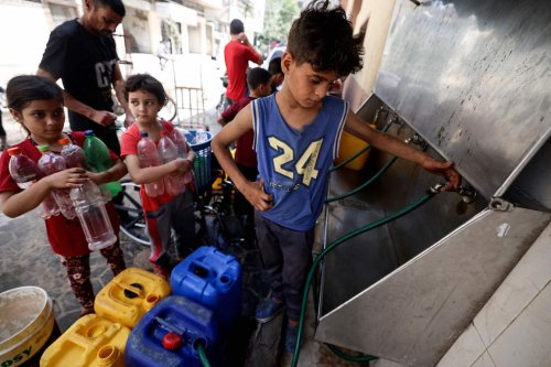 Palestinian children fill up gallons with water in Gaza City on 20 May 2021. [MAHMUD HAMS/AFP via Getty Images]