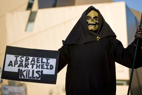 US left-wing activist protests against the construction of settlements in the West Bank outside the Bar Ilan university in Ramat Gan, near Tel Aviv, as Prime Minister Benjamin Netanyahu gave a keynote address in which he laid out his peace policy on June 14, 2009 [JONATHAN NACKSTRAND/AFP via Getty Images]