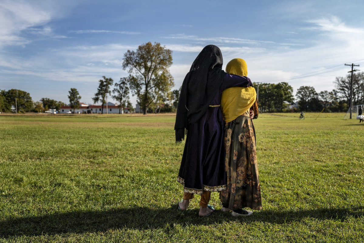Afghan refugee girls watch a soccer match near where they are staying in the Village at the Ft. McCoy U.S. Army base on 30 September 2021 in Ft. McCoy, Wisconsin. [Barbara Davidson/Getty Images]