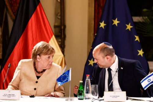 German Chancellor Angela Merkel and Israeli Prime Minister Naftali Bennett chat during a roundtable discussion with Israeli entrepreneurs in Jerusalem October 10, 2021 [RONEN ZVULUN/POOL/AFP via Getty Images]
