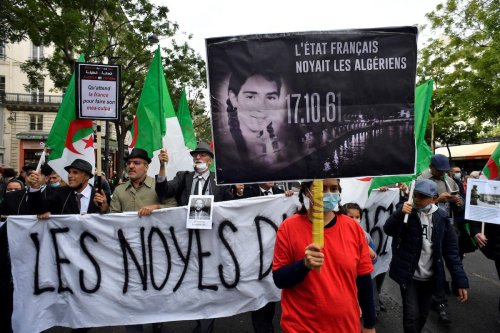 People hold placards and Algerian flags during a rally to commemorate the brutal repression of an Oct 17, 1961 demonstration during which at least 120 Algerians were killed during a protest to support Algerian independence, near the Pont Neuf bridge on 17 October 2021 in Paris. [ALAIN JOCARD/AFP via Getty Images]