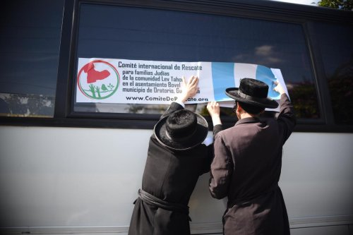 """Members of an Orthodox Jewish community put a label from the """"International Rescue Committee for Jewish Families of the Lev Tahor Settlement"""" on the window of a bus in Guatemala city on September 25,2016. [JOHAN ORDONEZ/AFP via Getty Images]"""