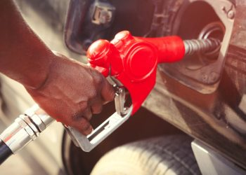 Detail of persons hand filling up the tank with nozzle in Africa