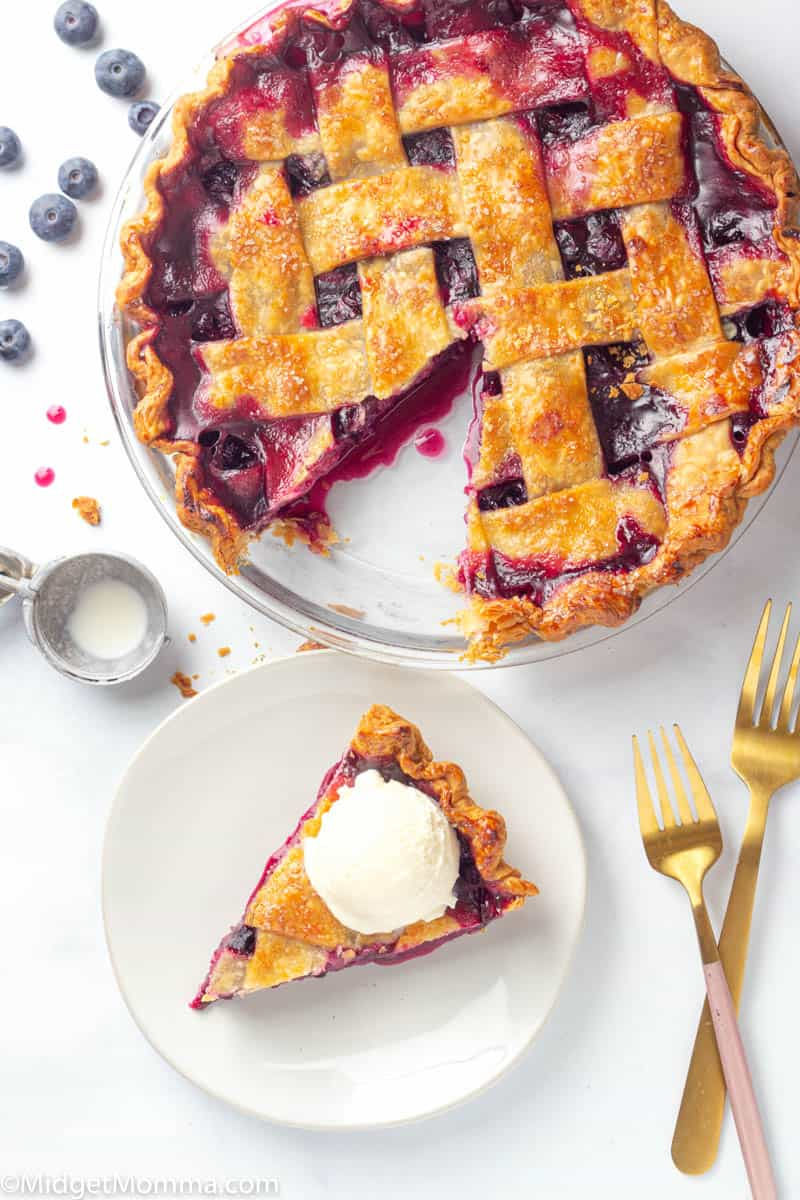 Slice of blueberry pie with ice cream on top