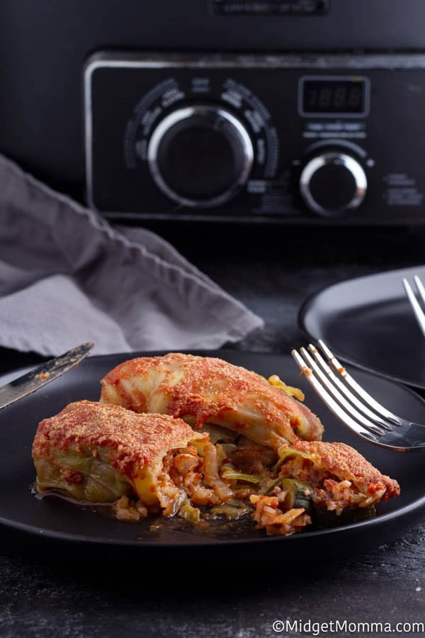 Crock pot stuffed cabbage rolls recipe cooked set on a black plate with a fork and knife