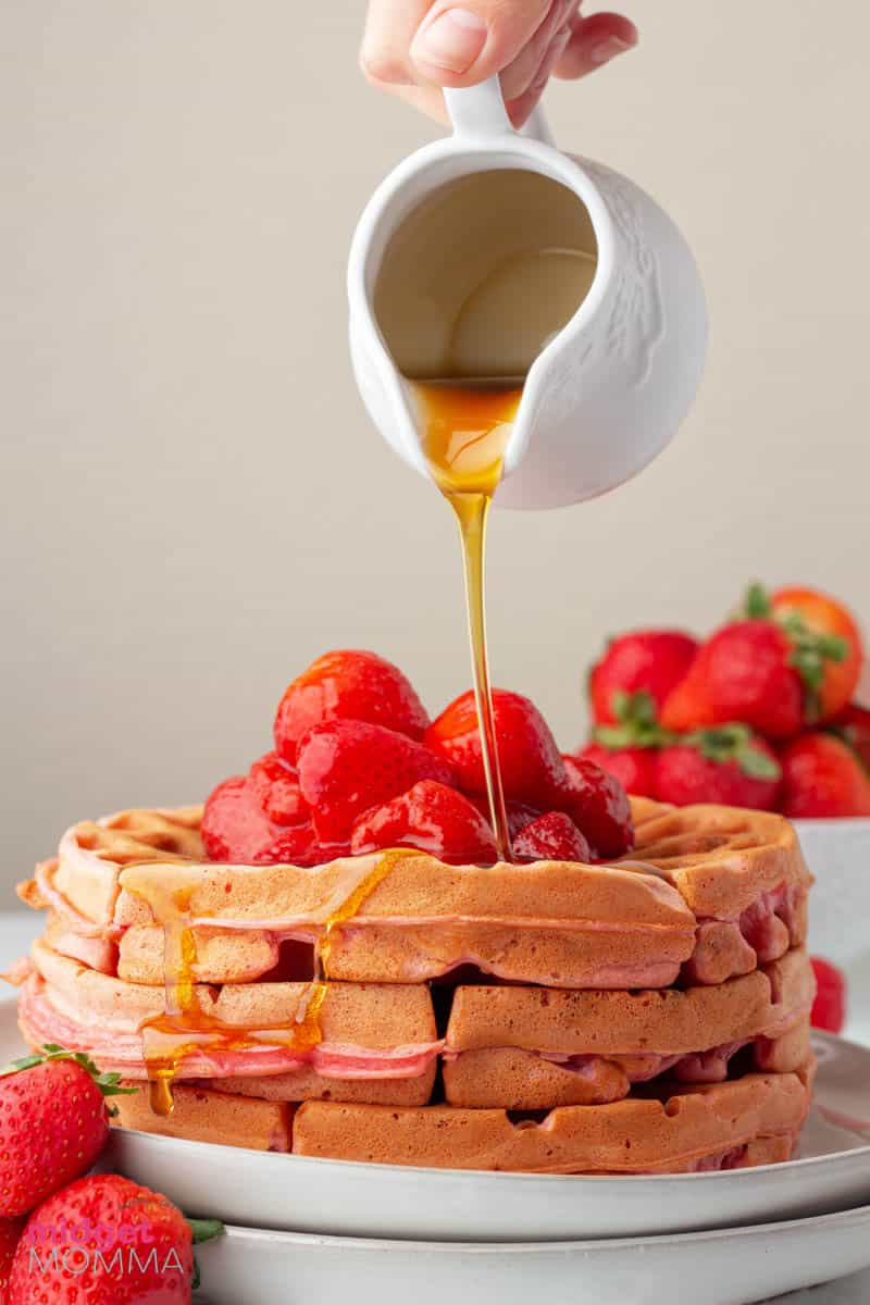 homemade strawberry waffles stacked on a plate with maple syrup being poured on top.
