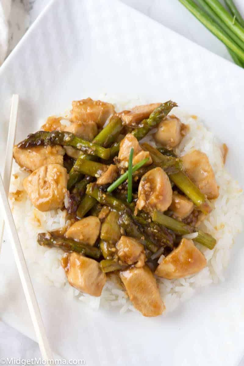 Plate of chicken and asparagus stir fry served over white rice