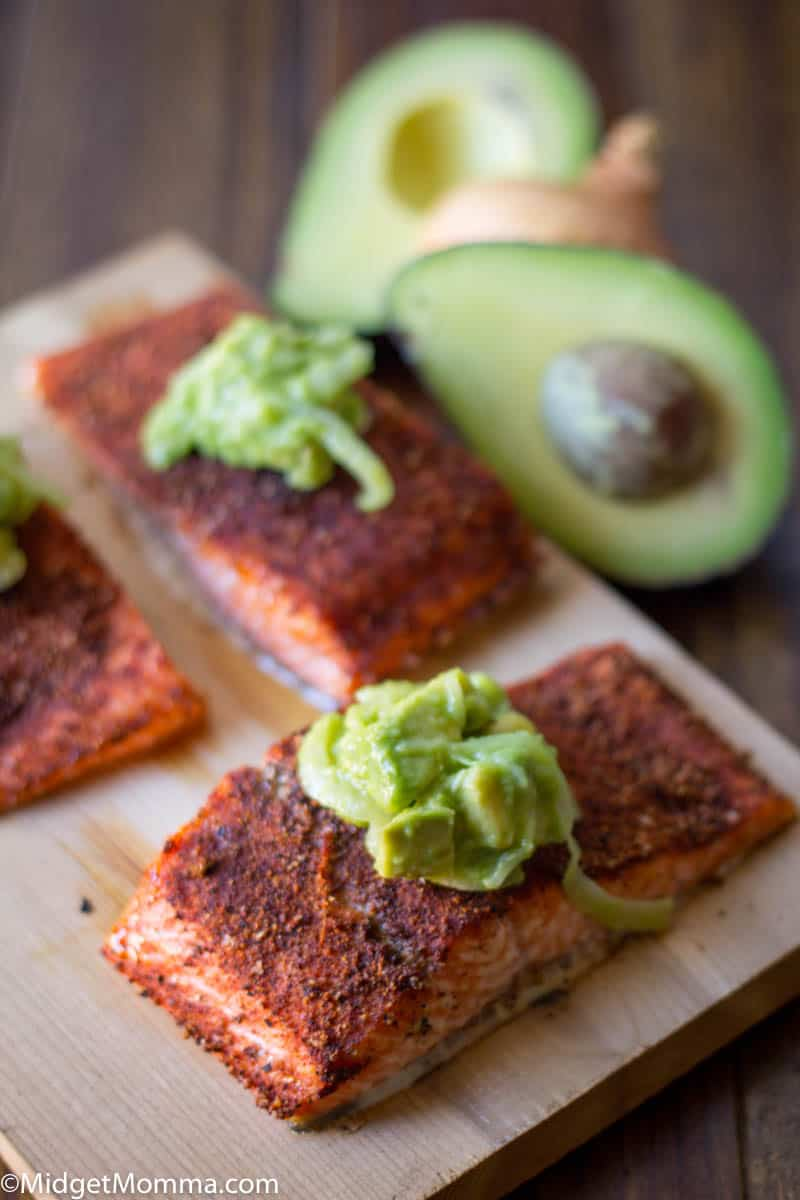 grilled salmon seasoned with spices and topped with avocado onion salsa on a cutting board
