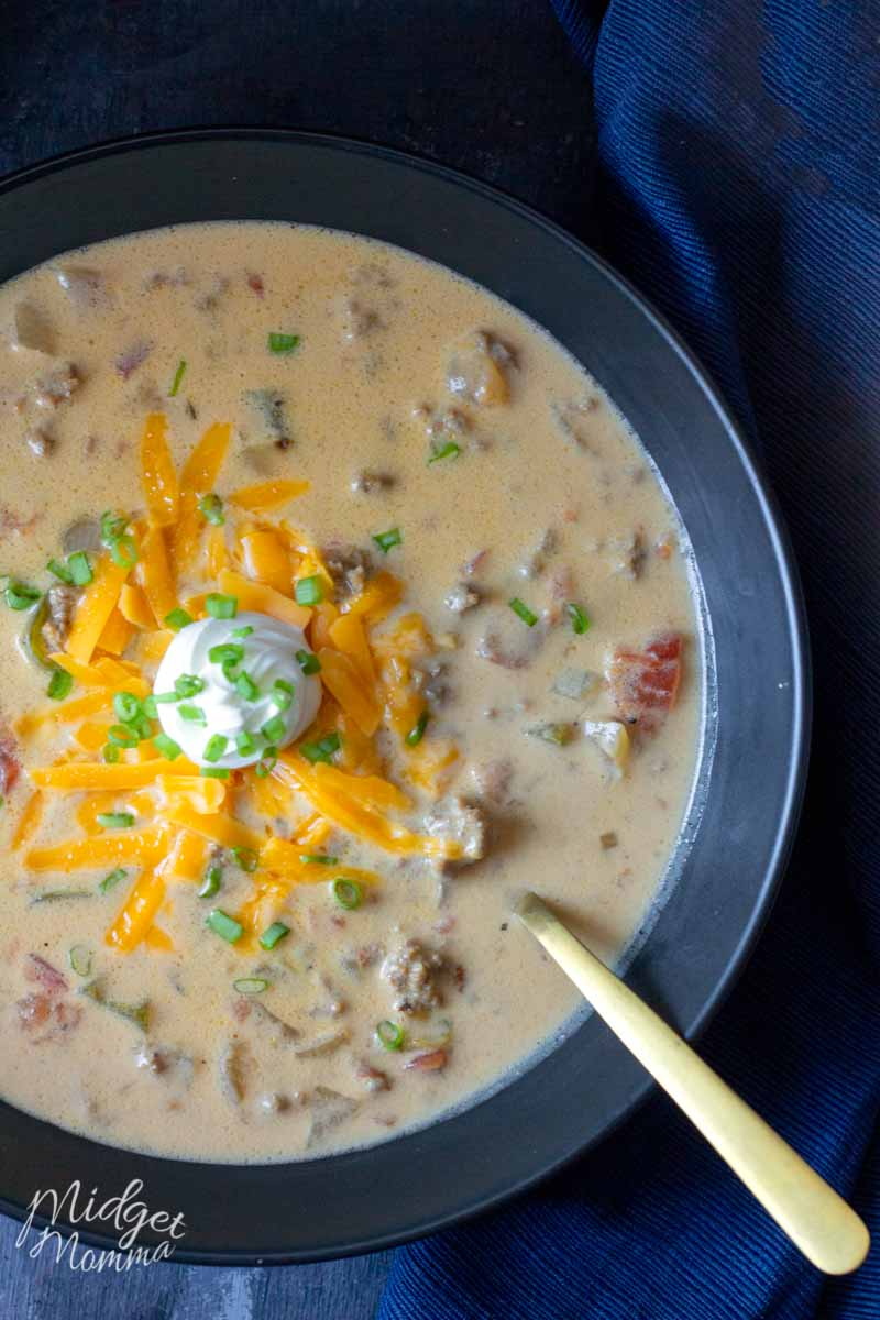 Cheeseburger soup in a bowl topped with cheese and sour cream
