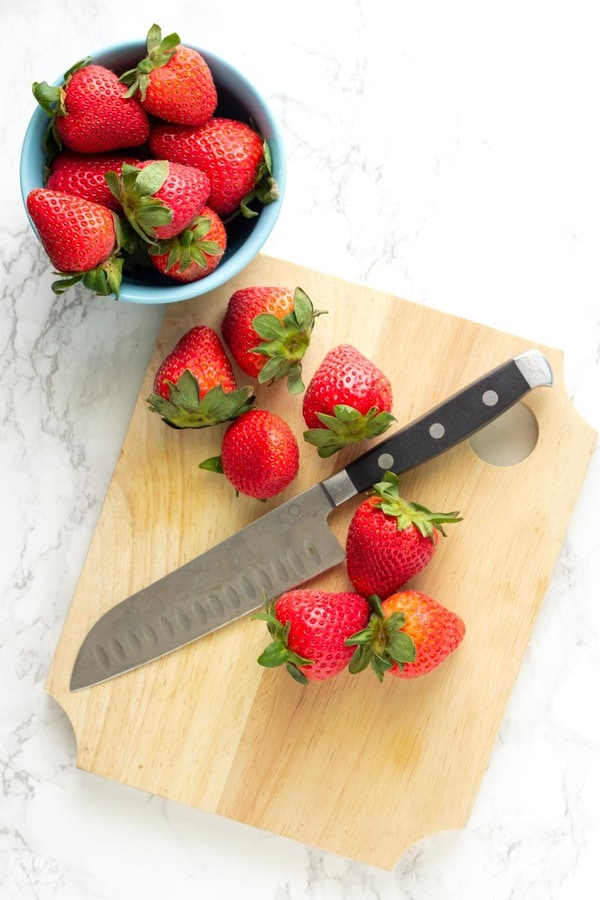 fresh strawberries on a cutting board to be cut to make low carb strawberry buttercream