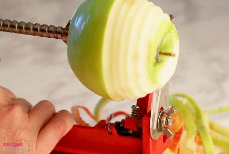 apple being peeled on an apple peeler